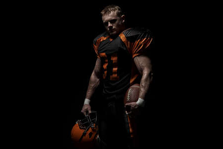 American football player on a dark background in black and orange equipment. Stock Photo