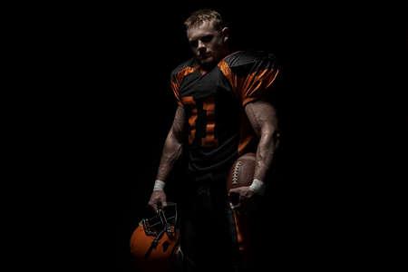 American football player on a dark background in black and orange equipment. 版權商用圖片