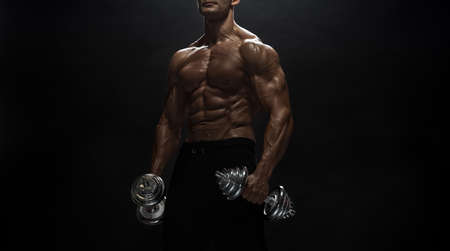 Fitness model Man posing in the studio. Dark background.