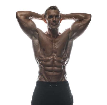 Fitness model Man posing in the studio. White background. Isolated. Reklamní fotografie