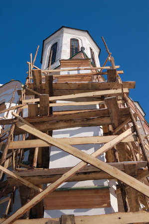 restoring: fragment of church in scaffolding  Stock Photo