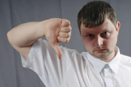 pollice in gi: triste uomo mostrando pollice verso il basso