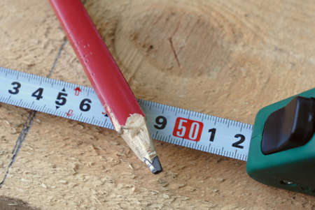 Green tape measure and red pencil drowed gray line on the light board photo