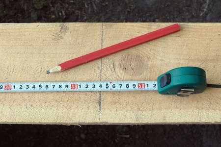 Pencil, tape measure, gray line of cutting and board from top view photo