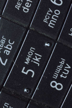 overexposed: Macro view of mobile phone keyboard. On the buttons are numbers and English letters. Buttons has black color and numbers and letters has white colors.