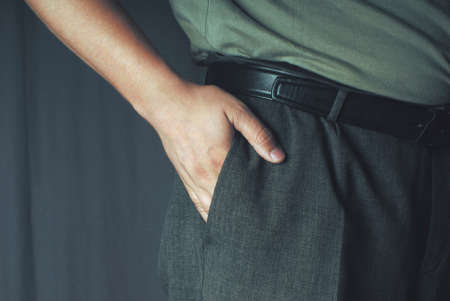 hand in pocket: Caucasian adult mans hand in gray cotton trousers pocket. Stock Photo