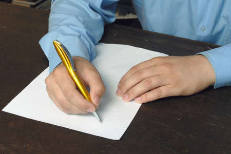 one sheet: Pair of males caucasian hands one of which holding golden pen near white sheet of paper lying on the brown old wooden table.