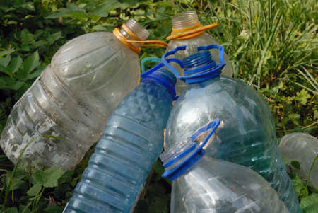 environment damage: Heap of five big plastic obsolete empty bottles lying on the green grass and to cause damage to the environment.