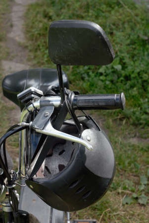 rearview: Gray and black helmet hanging on the silver moped helm. Also this moped has big rearview  mirror and triangle saddle.