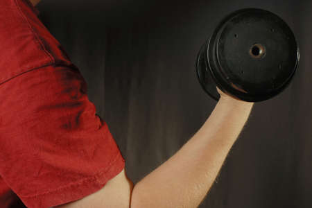 red tshirt: Human hand in red T-shirt holding black dumbbell. Gray background. Stock Photo