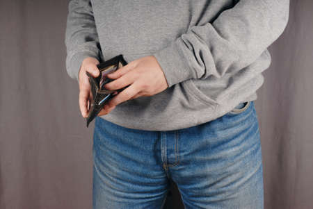 hoody: Man (we cant see his face) wearing blue classical jeans and gray hoody counting money in wallet. And thats the main question: is it his own wallet ? Or may be he is robber after robbery ? Stock Photo