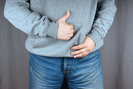 hoody: Man wearing blue jeans and gray hoody showing thumb up for us. He is really happy, we cant see his face but we sure that he is happy. Stock Photo
