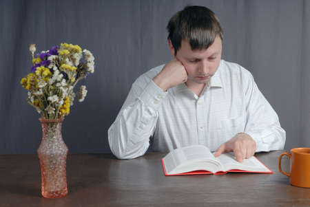 Young caucasian man wearing white shirt sitting at the old, wooden, brown table reading closely thick book with pink bookcover and drink tea from orange cup. Vase with beautiful flowers standing on the table too. Stock Photo