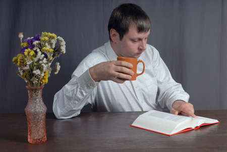 bookcover: Young caucasian man wearing white shirt sitting at the table and get a big pleasure doing two action at once: drinking delicious tea from big orange cup and reading thick book with pink bookcover. Vse with beautiful flowers standing on the table adds good Stock Photo