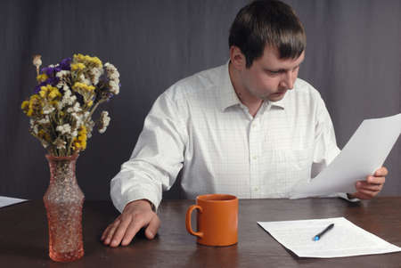 forgot: Young caucasian man thoughtfully read some important document printed on the white sheet of paper, He is so busy that forgot about cup of tasty tea and beautiful flowers in the vase standing on the table.