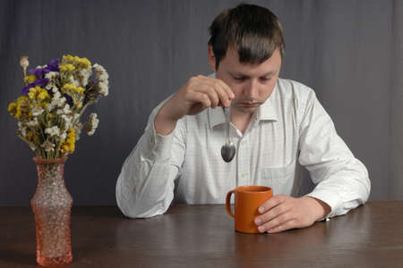 sittting: Young caucasian man wearing white shirt sad about something sittting with big orange cup of tea at the wooden, brown table and holding spoon in his hand. Even beautiful flowers in vase dont improve his modd. Stock Photo