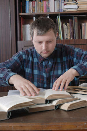 simultaneously: Young man wearing checkered shirt with great perseverance trying to find information what he need. He do this opened several books simultaneously.