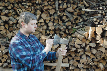 hatchet man: Young caucasian man in checkered shirt stands near high stack of firewoods and with the helping of  own fingers check the sharpness of his axe. Stock Photo
