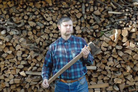 hatchet man: Young caucasian man wearing blue jeans and checkered shirt standing with long axe near high stack of firewood. But this doesnt mean that he hack this firewoods.