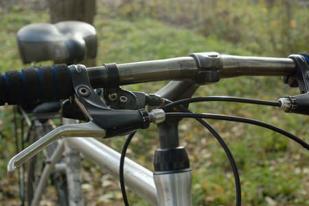 handlebar: Bicycle handlebar with couple of break handles. Bicycle staying outdoor.