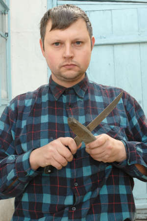 sharpen: Young caucasian man in checkered shirt holding knife and sharpener with the helping of which he going sharpen this knife.
