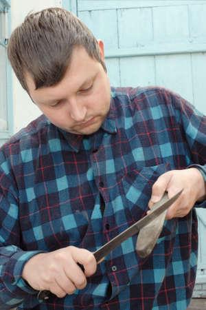 sharpening: Young caucasian adult man wearing checkered shirt sharpening steel knife. Stock Photo