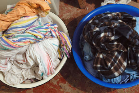 Two heap of multicolored clothes after washing lying in two round washbasins that staying on the floor.