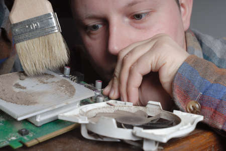 eye service: Caucasian aduld young man carefully cleaning computer graphic card with the helping of brush. Stock Photo