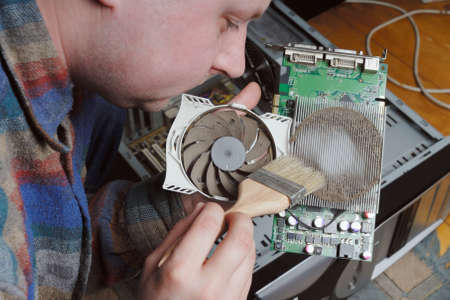 eye service: Adult caucasian man cleaning graphic card covered thick layer od dust with the helping of brush. PC with open case as background.