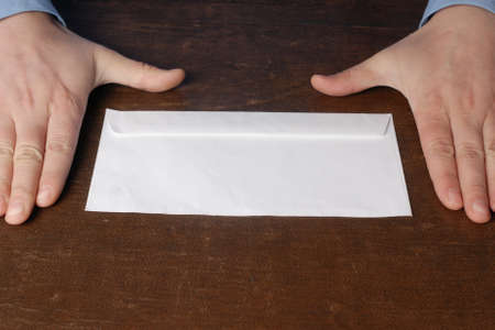 bribery: Pair of caucasian male hand in blue shirt lying on the old wooden brown table near  white rectangular envelope. Seems that there is good bribery in this envelope. Stock Photo