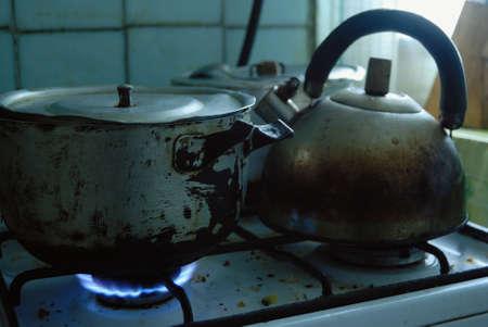 under fire: bandeja de metal sucio y hervidor de agua en la estufa. Hay fuego azul bajo un mismo molde. foto tomada en Ucrania.