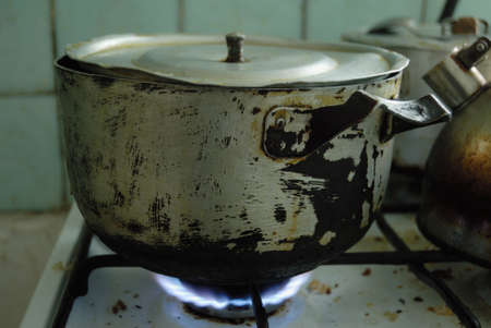 old gas stove: Something cooking in metal pan that staying on the gas stove.