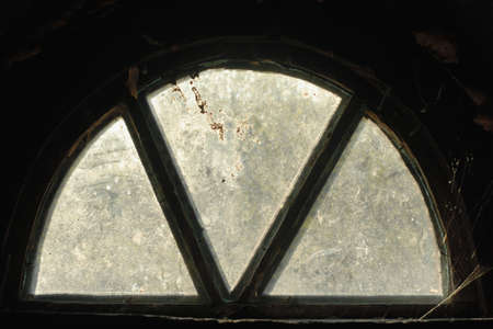 attic: Mysterious semicircle window in the attic with dirty glass. Photo shot in Ukraine, during sunset.