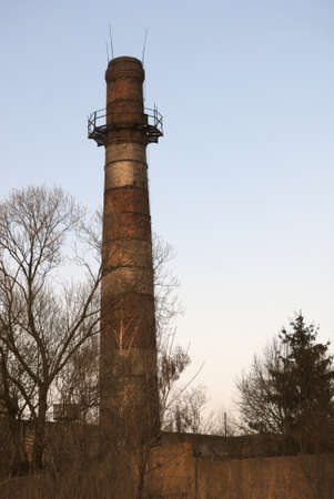 tall chimney: Gloomy scene with plant brick chimney, dark silhouettes of trees and blue sky.