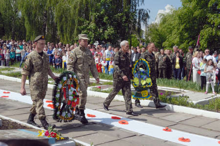 liberating: Ostroh, Ukraine - May 9, 2016: Veterans of USSR war in Afganistan (1979-1989) (R) and war of Russia against Ukraine (2014-) (L) honoring soldiers of Red Army that died in WWII during Ostroh liberating.