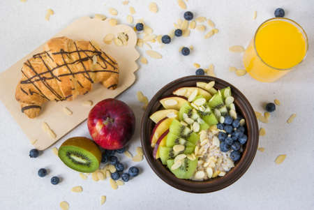 amended: Oatmeal with kiwi, apples, almonds and blueberries. Amended orange juice in a glass, croissant and fresh fruits. A healthy breakfast on a light table, top view