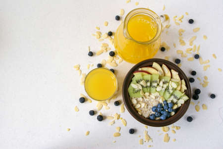 amended: Oatmeal with kiwi, apples, almonds and blueberries. Amended orange juice in a glass and fresh fruits. A healthy breakfast on a light table, top view, copy space Stock Photo