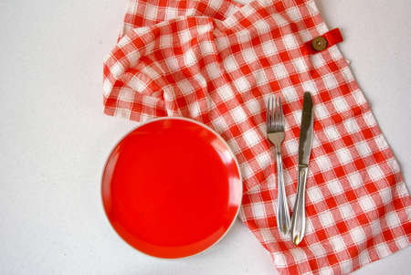 Background: white textured surface of the table, a tablecloth on it in red cell red plate Stock Photo
