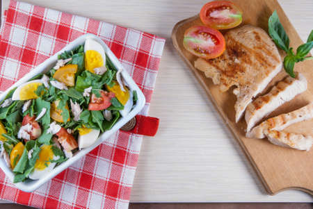 Chicken fillet, grilled, with a large portion of salad with fresh vegetables and herbs on a wooden table with a red cloth into a cell. top view Imagens - 62104557