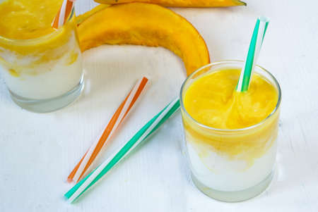 ombre: Ombre smoothie of yogurt and pumpkin puree: a refreshing drink that is pleasant to drink in the summer and autumn. On white wooden background