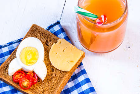 Funny breakfast for kid: sandwich with rocket cheese, eggs and tomatoes Stock Photo