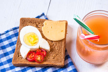 Funny breakfast for kid: sandwich with rocket cheese, eggs and tomatoes Reklamní fotografie