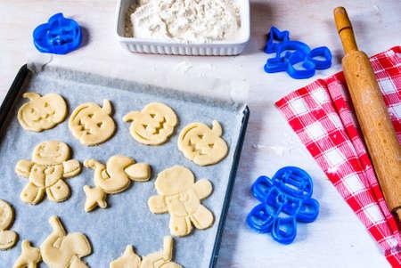 할로윈과 추수 감사절 쿠키 만들기. 아이들을위한 재미있는 음식, 파티를위한 간식. 흰색 나무 테이블에 반죽 반죽, 쿠키 커터, 롤링 핀, 밀가루, 수건 스톡 콘텐츠