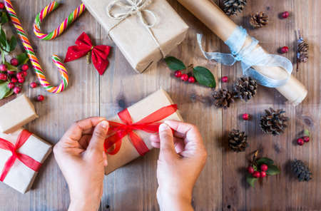 decorates: Girl decorates Christmas gift, ties red bow. On the table other gifts. Hands in picture, top view
