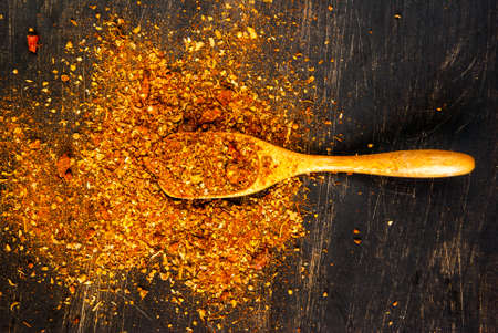 Stagionatura. Una miscela di spezie piccanti per cucinare, con un cucchiaio di legno per le spezie su un tavolo di legno nero. vista dall'alto, copia spazio Archivio Fotografico
