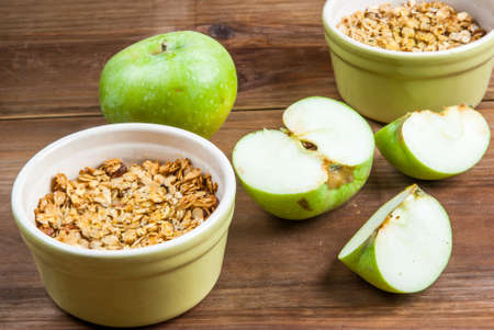 apple crumble: Freshly made autumn apple crumble with fresh green apples on a wooden table, top view Stock Photo