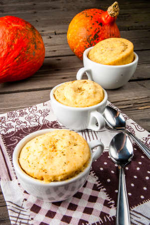 homemade cake: Pumpkin mug-cakes in rustic style, on an old wooden table, next to pumpkins Stock Photo