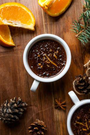 향신료, 오렌지와 오렌지 농담과 핫 초콜릿. 크리스마스 나뭇 가지, 콘, 오렌지의 배경. 나무 테이블