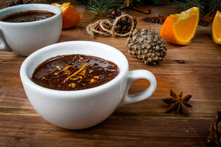Hot chocolate with spices, orange and orange zest. Against the background of Christmas tree branches, cones and orange. Wooden table
