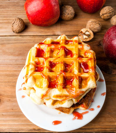 Autumn belgian waffles with apple jam, next to apples and nuts. On a wooden table. 版權商用圖片